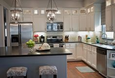 I love that they added glass-doored upper cabinets for a little extra storage of those things you'll not use frequently. This whole kitchen is pretty!