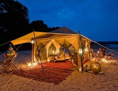 traditional bedouin beach tent with lanterns and outdoor dining