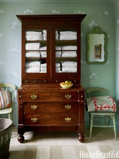 An antique mahogany secretary is repurposed as a linen press. The sisal rug was painted in broad stripes to add a graphic counterpoint to the walls.