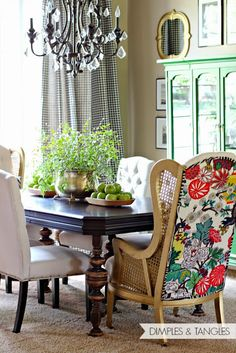 colorful Dining Room // green china cabinet // dark antique table // tufted upholstered chairs // Chiang Mai fabric on back of chairs // cane wingbacks // Audubon bird prints