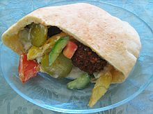 A pita filled with vegetables and fritters on a plate. I want to try this with Falafel.