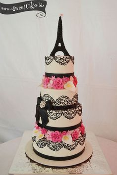 EIFFEL TOWER WEDDING CAKE    4 tier fondant wedding cake with sugar flower separators  fondant ribbon border and bow with a crystal brooch, hand piped lace and a sugar Eiffel Tower topper.