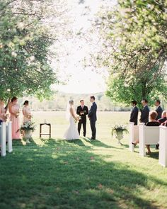 """White pews were set up in the orchard for the ceremony, with urns holding floral arrangements flanking the bride and groom. Musical selections included an instrumental version of Christina Perri's """"A Thousand Years"""" for the bride's procession, and """"Ho Hey"""" by the Lumineers as the couple walked up the aisle together as husband and wife."""