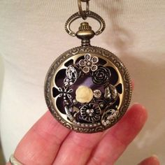 For this beautiful necklace I combined a floral pendant with an empty timepiece locket, fitted it with a leather pad, and hung it on a brass