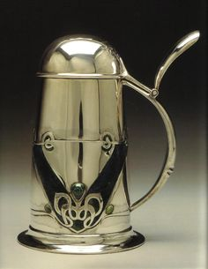 Designed by Archibald Knox (1864-1933)  was a Manx art nouveau designer of Scottish descent.  His design talent covered a wide range of objects, ornamental and utilitarian, and included silver and pewter tea sets, jewellery, inkwells, boxes, gravestones and even bank cheques, much for Liberty's Tudric (pewter) and Cymric (precious metals) ranges.