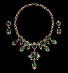 The gold filigree necklace is composed of X shaped links, each embellished with an old mine cut diamond between emeralds, meeting at the centre rectangular cut emerald flanked on each side by pairs of similarly cut emeralds hug with emerald drops. The large ornament hanging from the centre is mounted with a circular cut emerald framed in diamonds and emeralds with a pear shaped emerald drop below...(tbc)