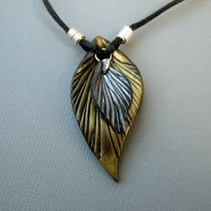 "A large bright gold on black leaf necklace with a smaller silver and black leaf dangle.  Each leaf is made by hand with black polymer clay that is cut, textured, shaped, cured, and highlighted with colored mica powders.  The findings are hand-coiled and shaped from silver plated non-tarnish copper wire.    Leaf size:  2"" (5 cm) long x 1"" (2.5 cm) wide 