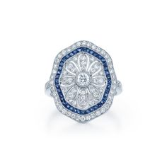 A halo of bright sapphires and vivid diamonds encircle the blooming daisy center.