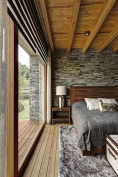 This bedroom is magnificent and the window is spectacular. It's all about texture: the ceiling and walls, layered rug, and the smooth pane of glass, and then the view which has textures all its own!