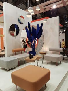 Neutral tones contrast with strong blue plant feature Milan Furniture Fair exhibition stand