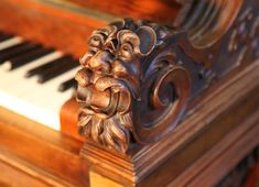 An art cased, Ehret upright piano with an ornately carved, rosewood and walnut case. Cabinet features carved heads on piano cheeks and brass candlesticks.