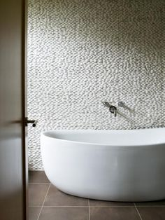 Gustave Carlson Design plays up textures in a Palo Alto bath, placing a stone wall behind a sculptural tub.