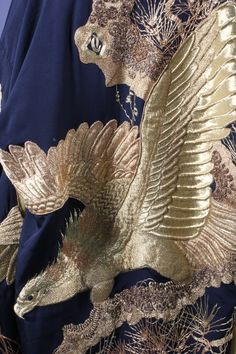 Two embroidered kimono, Japanese, 1930s, of black silk, one adorned with detailed raisework embroidery of an eagle, the other with couched silver coiling dragons