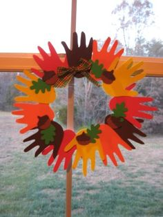 Trace your student's hands on fall-colored construction paper or thin sheets of colored foam and cut them out. Glue the hands on a large circle. (You can cut out the center of a paper plate for this and leave about an inch thickness around the edges.) Glue decorations such as acorn shapes and a bow, as well as a piece of yarn to use to hang it.
