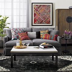Dark rug, grey couch, and pops of color with a modern southwest vibe