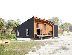 Houten huis met zwarte rubberen huid - Architectuur.nl