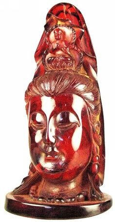 Carved translucent golden amber Kuan Yin, Chinese Goddess of Mercy, the eyes closed in meditation. On her crown, an image of Buddha in prayer. 1700's AD
