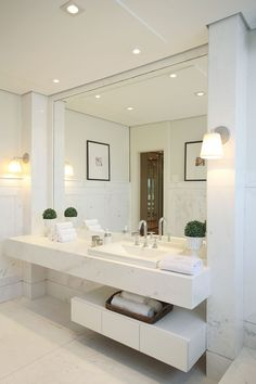 White bathroom, modern and clean design, large full wall covering mirror and single vanity