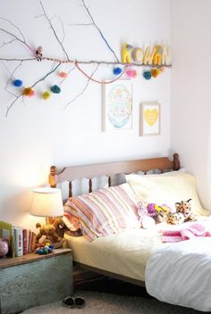 Pompoms and yarn wrapped sticks make a creative piece of art for a little girl's room or craft studio.