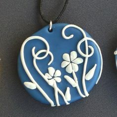 Cobalt Blue in color with white flowering vines. Its fun, and detailed, and will make a great addition to your jewelry collection