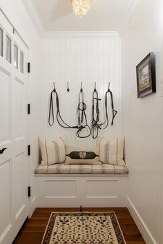 Tiny Mudroom with Built-Ins Behind Front Door | The home is full of character and thoroughbred details, including this paneled foyer nook with a built-in bench. The story of the equestrian family who resides here is all in the details.