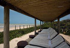 Um pergolado feito com toras de eucalipto serve de apoio na praia e cobre as espreguiçadeiras de madeira. Dá para curtir a vista sem se expor totalmente ao sol