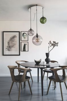 dining room in nordic apartment, gallery wall, design chairs and glass ceiling lamp
