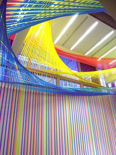 los angeles-based artist megan geckler has created a site-specific architectural installation at the wexner center for the arts   in columbus, ohio. constructed from interlacing strips of vibrantly colored flagging tape, the work entitled  'spread the ashes of the colors' hovers above and surrounds visitors in the institution's café and lobby areas.
