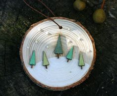 Five little wooden trees painted in green glitter watercolors dance in the pearly white snow Hang from your tree or on a wall for more art