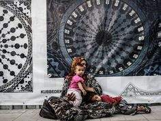 """A Syrian woman begs with her children downtown Istanbul. Turkey is to take """"drastic measures"""" to deal with the influx of tens of thousands of Syrian refugees into its biggest city Istanbul, including forcibly sending them to camps in the southeast"""