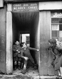 Children playing at the entrance to McGee's Court slum on Camden Street, Dublin, Ireland, 1948. By Tony Linck.