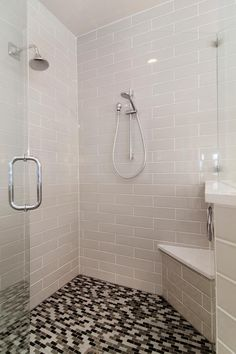 This glass enclosed master bathroom shower boasts neutral wall tiles paired with brown, black and neutral mosaic floor tiles. A corner bench provides a convenient spot for relaxing while showering.