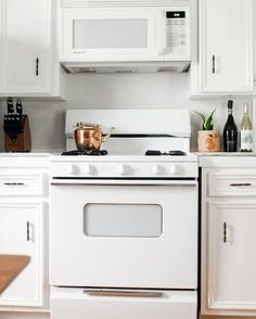 From Wayfair Canada, this image features a small kitchen with white cabinets and white appliances. The gold teapot contrasts with the white stove, making it a cute focal point.