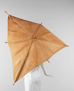 Elsa Schiaparelli parasol from 1937-1940. The asymmetric shape is indicative of Schiaparelli's desire to design objects with an artistic quality. Bamboo, a wood more traditionally used for parasol handles, is used for the ribs, an unexpected twist. The canopy material, more commonly silk, cotton or linen, has the appearance of straw, again evoking the idea of a straw hat. The overall effect is very eye-catching and chic.