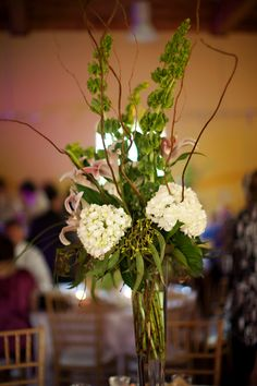 Bells of Ireland, Willow Branches, White Hydrangea and Pink Lilies in a Tall Cylinder Vase http://busseysflorist.com/wedding-flowers/