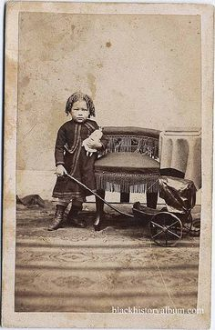 Full length portrait, young AFrican American girl standing by a tassled chair, holding doll and handle of baby doll carriage, ca. 1870. Randolph L. Simpson African-American collection. Beinecke Rare Book and Manuscript Library, Yale University. Vintage African American photography <3
