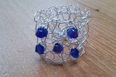 """Een echte """"weer s wat anders ring"""". Zo'n ring heeft u vast nog niet. Een prachtig sieraad voor uw vinger, deze ring met de hand gebreid met verzilverd draad en blauwe swarovski kristalletjes."""