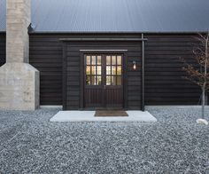 Wakatipu Basin house by Bureaux Architects - detail of dark timber cladding with silver roof