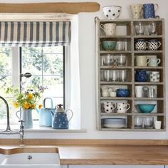 Key country pieces, such as a the butler sink and exposed beams, add authentic charm, while individual personality is introduced with antique pieces like these pigeon hole shelves filled with rustic crockery