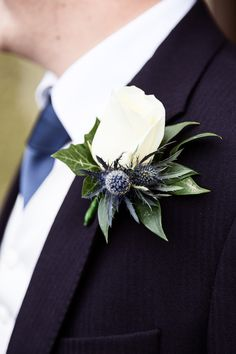 Groom's button-hole: traditional white rose centre with additional blue/thistle flowers to go with Navy Blue suit & cravat. Best Man & Bride Father - similar button-holes but smaller and less ornate.