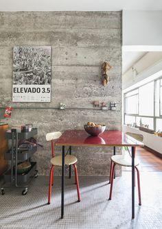 Parede de concreto, mesinha vermelha e cadeiras metálicas garimpadas.