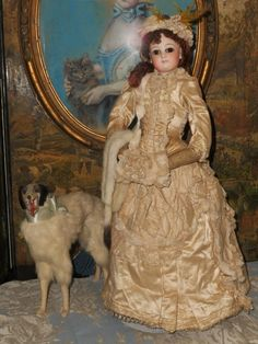 Outstanding French bisque poupee by Emile Jumeau ..... France circa 1870. Wearing absolute wonderful of champagne color two piece silk couture winter afternoon gown with matching bonnet and muff , set of under-garments , light pink socks and shoes .