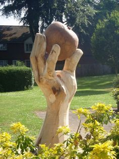 Existing tree and imported wood Outsize, Very Big, Extra Large and Massive sculpture by artist Nigel Sardeson titled: 'Isaacs Apple (Giant Carved Wooden Hand and Apple statues/Carving/Art)'