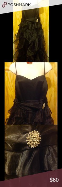 """Vintage Torrid Black Formal Chiffon Dress NWT Vintage formal Torrid black chiffon waves gown. It has a satin bodice with spaghetti straps and a back zipper. The skirt is floor length and has multiple  and diagonal layers of chiffon. Detachable rhinestone pin at hip. The bust measured flat is 21"""", waist is 18"""" and the skirt from waist to floor is 50"""". Never worn with tags. It has been hanging in my closet for a while and needs to be dry cleaned before wearing. I live with two cats but all…"""