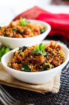 Italian Quinoa    2 28 ounces cans whole peeled tomatoes  4 cloves of garlic, peeled and sliced  2 tablespoons olive oil  8 ounces sausage or tempeh sausage  3 cups cooked quinoa  2 ounces baby spinach  For topping (optional): Grated parmesan cheese OR vegan parmesan