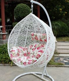 Fancy Decorative White Outdoor Wicker Hanging Chair With Pink Floral  Pillows Set On Stoned Floor Plus
