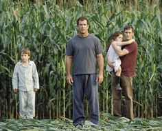 Signs - Graham Hess (Mel Gibson, center left), along with his son, Morgan (Rory Culkin, left), his daughter, Bo (Abigail Breslin, center right), and his brother, Merrill (Joaquin Phoenix, right), investigate the strange occurrence.