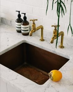 The copper sink, Carrara marble worktop and @perrinandrowe Aged Brass taps by deVOL all work together to make this kitchen feel simple and beautiful.#deVOLKitchens