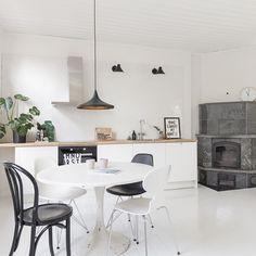 Viihtyisä vaalea avokeittiö yhdistää mustan, valkoisen ja puun. Tilan kulmassa vuolukivi takka pitää huolen lämpimästä ja kodikkaasta tunnelmasta.