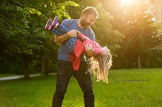 Father spinning his daughter in circles - Devoted father spinning his daughter in circles, bonding, playing, having fun in nature on a bright, sunny day. Parenthood, lifestyle, parenting, childhood and family life concept.